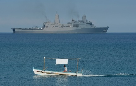 """A Filipino fisherman is seen past the US Navy amphibious transport dock ship USS Green Bay (LPD-20) during an amphibious landing exercise on a beach at San Antonio in Zambales province on April 21, 2015, as part of annual Philippine-US joint maneuvers some 220 kilometres (137 miles) east of the Scarborough Shoal in the South China Sea. The Philippines voiced alarm April 20 about Chinese """"aggressiveness"""" in disputed regional waters as it launched giant war games with the United States that were partly aimed as a warning shot to Beijing. AFP PHOTO/TED ALJIBE        (Photo credit should read TED ALJIBE/AFP/Getty Images)"""