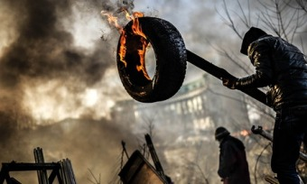 An anti-government demonstrator builds a barricade in Kiev